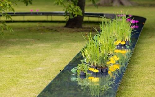 水路には造花と本物の植物を混ぜて置いた。草花の姿が水路に鏡のように映る。造花などを配置したのは、水を分岐させて流れをよくしたり、建材同士のジョイント部を隠したりする目的がある(写真:北山 宏一)
