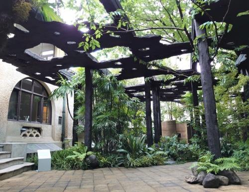 スパニッシュ様式の邸宅「kudan house」の庭園に、焼きスギの黒い屋根を架けた(写真:日経クロステック)