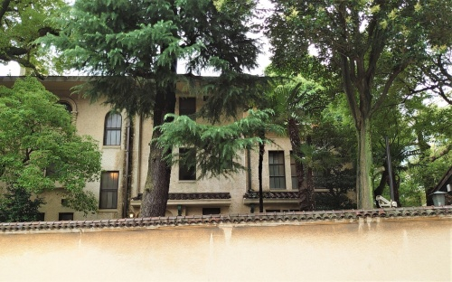 前面道路から壁越しにkudan houseを見る。洋館の周りには、森のように高い木が生えている(写真:日経クロステック)