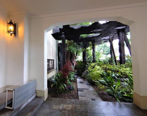 門をくぐって進んだ先にある、kudan houseの玄関。前方には既に、焼きスギの屋根と柱が見えている(写真:日経クロステック)