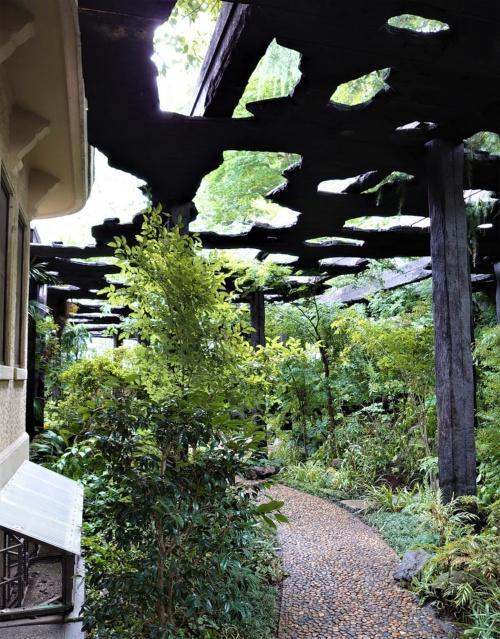 邸宅に沿って左にカーブする庭園の小道。焼きスギの屋根には無数の穴が開いている(写真:日経クロステック)