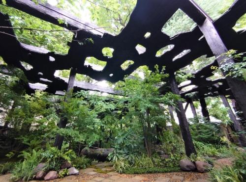 深い森のような庭園に、いつつくられたのか分からないような焼きスギの屋根が覆いかぶさっている(写真:日経クロステック)