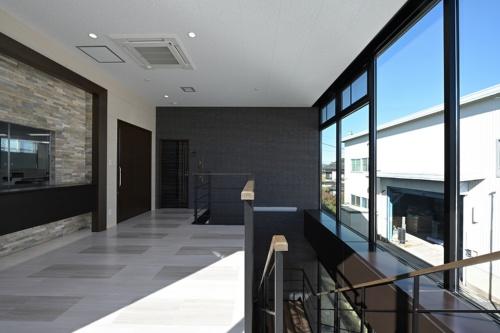 2階の階段ホール。日差しを取り込んだ明るい空間を通って事務所スペースに向かう(写真:須山建設)
