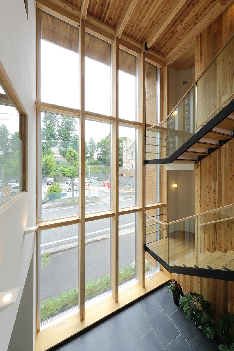 吹き抜けホールの大開口。断熱アルミサッシのカーテンウオールの内側に、造作で木の枠を取り付けた。右手の階段回りの壁にCLTを用いた(写真:材惣DMBホールディングス)