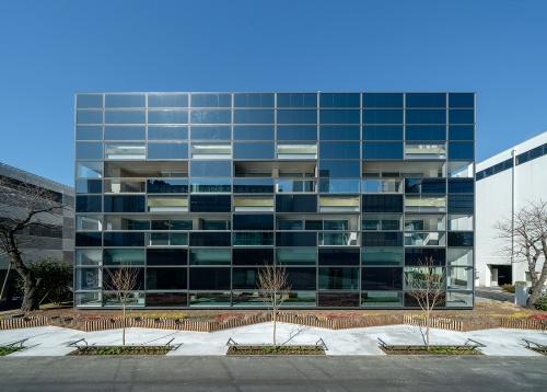 大成建設の技術センター内に建つZEB実証棟「人と空間のラボ」南側外観。窓以外の外壁に設置した太陽光発電パネルを高効率なタイプに一新した(写真:大成建設)