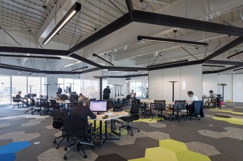 3階の執務エリア。天井のアンビエント照明とスタンド式のタスク照明は、空間設計を意識したデザインにした(写真:前田建設工業)