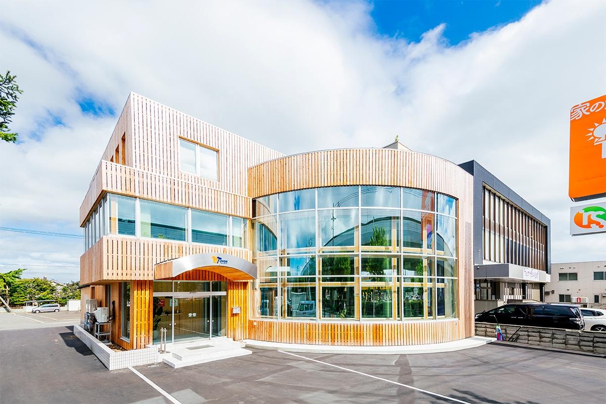 カラマツ張りに一新した棟晶新社屋の外観。扇形の建物部分は、南西に開いたアール状の大開口を持つ(写真:棟晶)