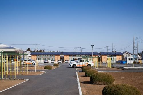 運転練習場越しに見る「土浦北インター自動車学校 校舎棟」の西側外観。手前に並ぶ3棟の屋根上に太陽光発電パネルを載せている(写真:吉田 誠)