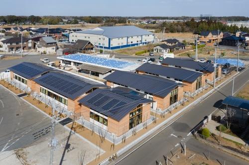 「土浦北インター自動車学校 校舎棟」の全景。梁間(はりま)8.4mの切り妻屋根の棟が6つ並ぶ。今後は、青いシートを載せた旧校舎を建て替えてレストランと合宿所を新設する(写真:吉田 誠)