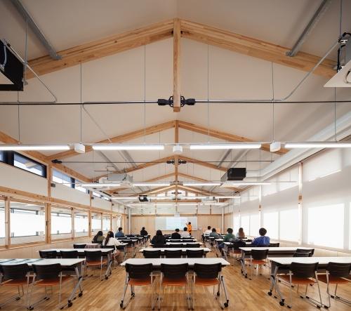 教室内観。登り梁(のぼりばり)と丸構の下弦材で構成した張弦梁を架けて、梁間8.4mの大空間を設けた(写真:吉田 誠)