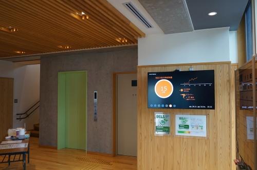 1階ロビー。地中採熱量などの各種データをデジタルサイネージで表示している(写真:守山 久子)