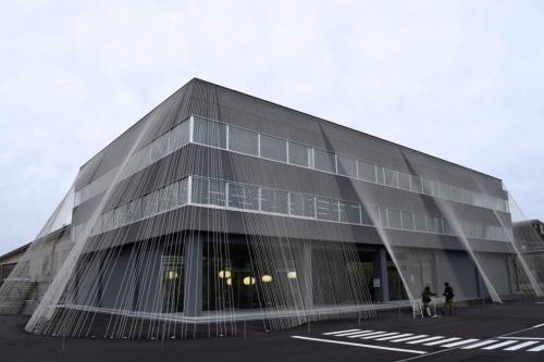 小松精練の旧本社棟を耐震改修して展示体験型の施設にリニューアルした。建物を取り巻くカーテンのドレープのように炭素繊維複合材料を張り巡らせた(撮影:日経アーキテクチュア)