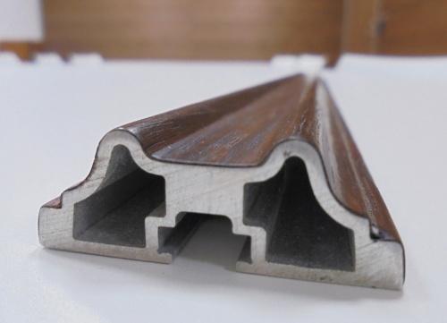 木の風合いを備えた内装の壁材。薄い木のシートをアルミ合金の押し出し材に貼って作っている。