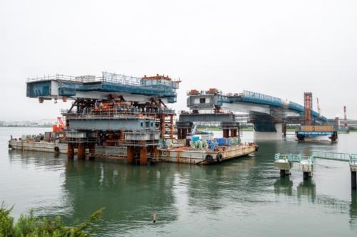 多摩川左岸から見た台船架設の様子。架設した桁は長さ42.5m、重量681t。午前5時前に台船の移動を開始し、桁の荷重を午前8時までに架設済みの桁とベントに受け替えた。2020年7月21日撮影(写真:大村  拓也)