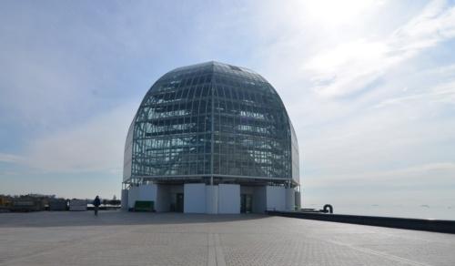 東京・江戸川にある都立葛西臨海公園内に立つ葛西臨海水族園。谷口吉生氏が設計した。シンボルとなるのが、海と水盤を背景に来園者を迎え入れるガラスドームだ。2020年2月12日に撮影したときはメンテナンス工事が行われていた(写真:日経アーキテクチュア)