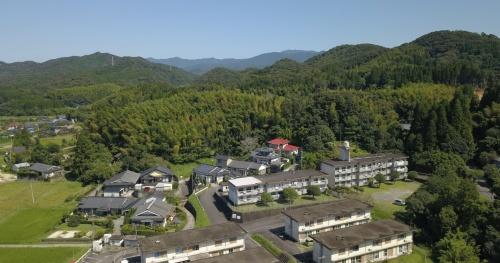 鹿児島県薩摩川内市営の集合住宅の1戸で、地元の竹を原料とするCNF(セルロースナノファイバー)を活用した建材を設置し、実験を行っている。写真中央に広がる薄い黄緑色の林が放置された竹林(写真:環境省)