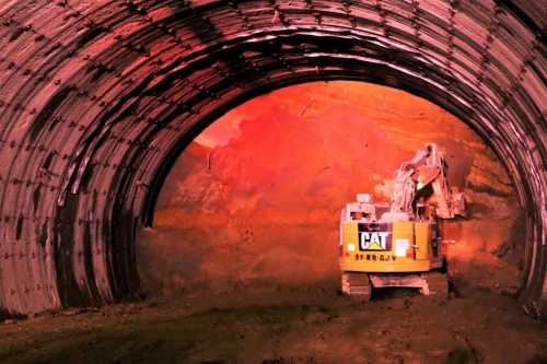 熊本県阿蘇市で清水建設JVが施工中の滝室坂トンネルの坑内。切り羽付近の重機の作業エリアに許可されていない作業員が侵入すると、自動で照明の色が切り替わったり、警告音が鳴ったりする(写真:日経コンストラクション)
