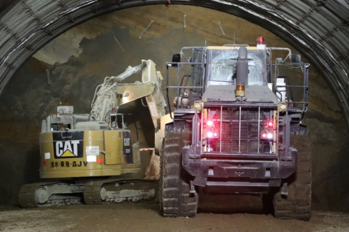 山岳トンネルの現場では、狭い坑内で作業員や大型の重機が交錯する(写真:日経コンストラクション)