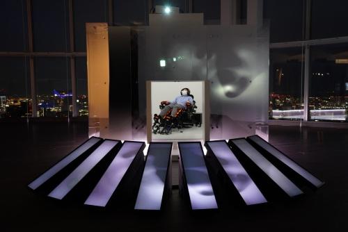 長椅子型装置「シナスタジア X1-2.44」(中央)は、六本木ヒルズ森タワー52階のガラス張りの空間に設置された小部屋の中にある