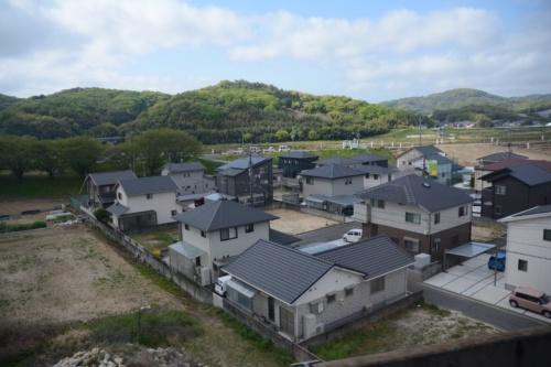 岡山県倉敷市を流れる小田川の堤防の背後に並ぶ住宅街。2018年の西日本豪雨で5mほど浸水した区域だ。2021年4月中旬に撮影(写真:日経クロステック)