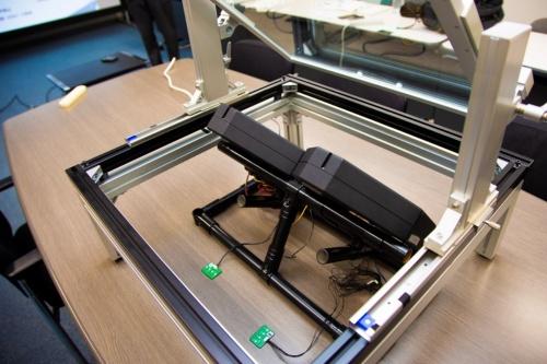 試作HUDを斜め後ろから撮影。手前側からガラスに表示した虚像を見る。(撮影:日経クロステック)