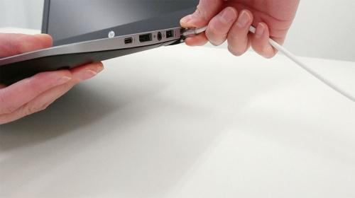 片手でノートパソコンを持ち上げ、ラッチレバーをしっかりと押し込んでから抜く