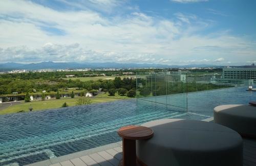 長辺が60mある、ホテルの最上階に位置するインフィニティプール。眼下に広がる緑は、国営昭和記念公園(写真:日経クロステック)