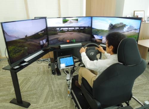 名古屋市の某所にある車両を、ソリトンシステムズの新宿オフィスからリモート運転する筆者。走行するのは自動車教習所の跡地の私有地。目の前のディスプレーには、前方(上に後方映像)、死角となるピラーを除去して合成した左右の映像が表示されている。車両が搭載するジャイロセンサーが感知した平衡知覚やステアリングのトルク、マイクが拾った音などのデータが送信され、操縦席にフィードバックされる