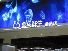 北京市内の十里堡地区にある、アリババの食品スーパー「盒馬鮮生」の北京1号店(左)と盒馬鮮生のロゴ(右)