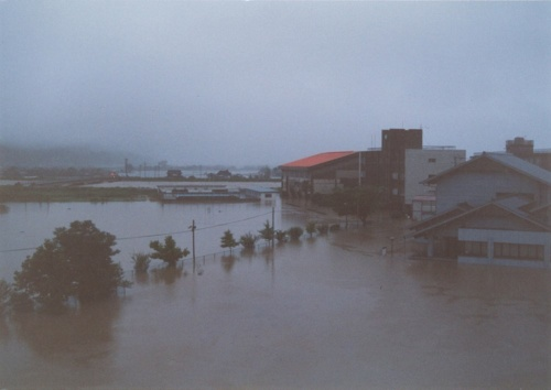 1990年夏の大水害で被災した、建て替え前の佐賀県嬉野市立塩田中学校付近の様子。右奥に見える赤い屋根や茶色の建物が体育館や校舎だ。大水害の際に同校周辺は1m程度浸水した。旧校舎はこの際、床上浸水の被害を受けた(写真:嬉野市教育委員会)