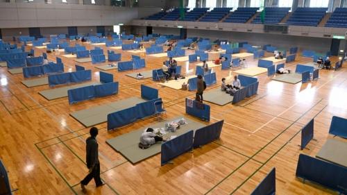 令和2年7月豪雨の被害を受け、熊本県人吉市に設けられた避難所に身を寄せる住民。新型コロナウイルス対策として、簡易的なパーティションを設けて、相互の間隔をとっている。避難所は感染症リスクと隣り合わせの空間だ(写真:毎日新聞社/アフロ)