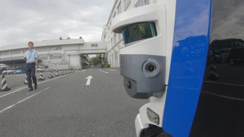パナソニックの本社構内では、人と自動運転の小型EVが共存していた。車両に設置したセンサーで人を検知すると、状況に応じて車両を停止させたりする。写真の右側に映っているのが小型EV車のセンサー部。(出所:パナソニック)