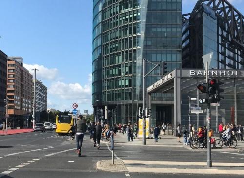 ドイツ・ベルリン中心部のポツダム広場。横断歩道を電動キックボードに乗った人が走っている