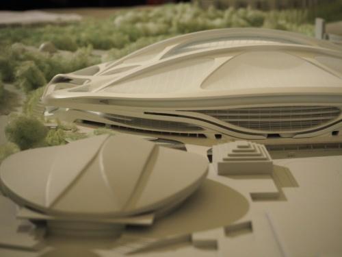 故ザハ・ハディド氏の設計による「新国立競技場」の模型(奥)。橋梁のような構造の「キールアーチ」を意匠にも生かすデザインだった(写真:日経 xTECH)