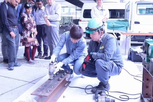 鋼構造物の亀裂を補修する工法を体験する学生。重い工具を両手で支えながら、ボルトの締め付け具合を調節する(写真:日経コンストラクション)