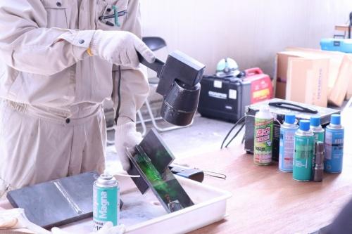 鋼構造物の表面の亀裂や傷を検出する技術の実演。ブラックライトを照射すると、欠陥部分に吸着した蛍光磁粉が光る(写真:日経コンストラクション)