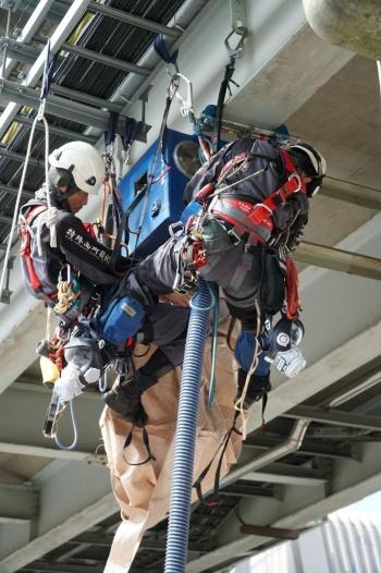 鋼橋の下フランジに開発した防護設備を取り付ける様子。6月13日に、首都高速道路会社の羽田補修基地でデモンストレーションを実施した(写真:日経コンストラクション)