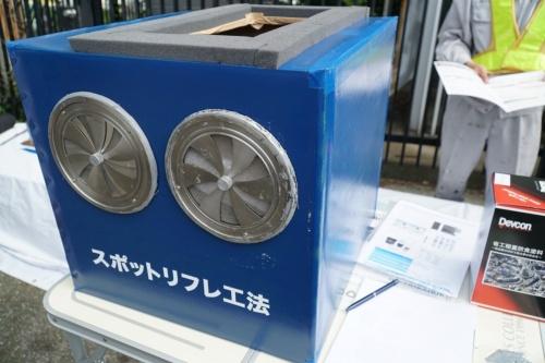 開発した防護設備の箱。スポンジが付いた開口部を腐食した面に密着させる。手前のファンを開閉することで、バキューム時の箱内の圧力を調整する。デモンストレーションの場で「リフレくん」と名付けられた(写真:日経コンストラクション)