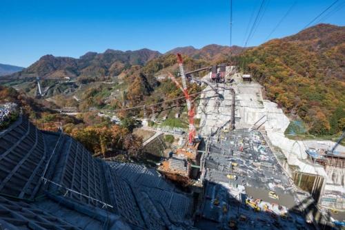 群馬県で建設中の八ツ場(やんば)ダムでは、「やんばツアーズ」と名付けた現場見学会に力を入れている。写真左端にコンクリートの打設が進む堤体を見下ろす見学者の姿。2017年11月撮影(写真:大村 拓也)