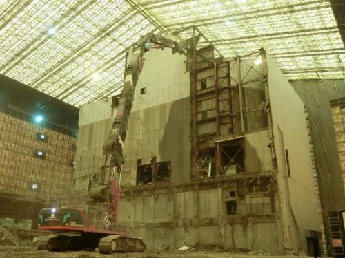 テント内で稼働する大型重機。アームの長さが35mある最大級の解体機を現場に導入した(写真:タクマ・鴻池JV)