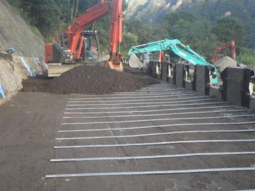 施工の様子。右手の壁面部材から背面の盛り土に補強材を水平に挿入する「テールアルメ工法」を採用した。土と補強材を幾層にも積み重ねる。補強材として、溶接構造用圧延鋼材(SM490A)に亜鉛メッキを施したものを使用した(写真:国土交通省関東地方整備局)