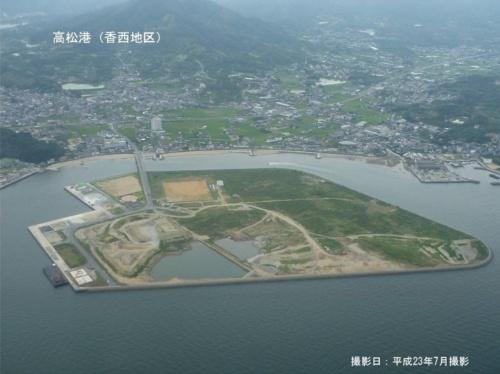 """クレーン大手のタダノが香川県から購入した高松港香西西地区埋立地の造成中の航空写真。完成後に埋め立て地の一部が陥没した。敷地の地中に埋まっている「内護岸」が原因となった可能性がある。タダノ総務部は写真中央に見える""""桟橋""""のような部分が内護岸だと説明する(写真:国土交通省四国地方整備局)"""