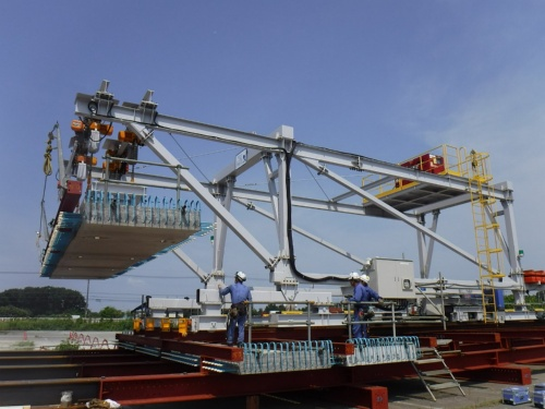 架設機でPCa床版を設置する実証実験の様子。幅員10m程度の実物大模型で実施した。門形フレーム内に搬入した床版は、運搬台車に装備してある回転台で90度回してから吊り上げる。玉掛けにはロボットを使用。作業員の墜落を予防する。門形フレームの組み立てには半日~1日ほど要する(写真:鹿島)