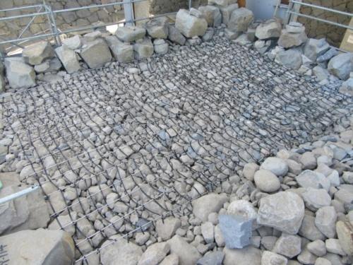 栗石(ぐりいし)層の中にグリグリッドを敷いた熊本城天守台の石垣の積み直し工事現場。小天守の入り口付近(写真:熊本市)