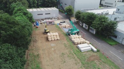 飛島建設は現場で防振堤の効果を検証した。地表面に敷き鉄板やコンクリート板を敷き、大型土のうを積むというシンプルな構造なので、撤去も容易だ。建設現場で使う資機材を活用するため、調達しやすく費用も抑えられる(写真:飛島建設)