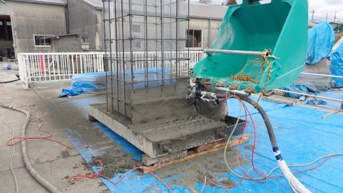 柱用の埋設型枠を造形している様子。垂直に組んだ鉄筋に金網を張り、そこにモルタルを吹き付ける(写真:日本建設機械施工協会施工技術総合研究所)