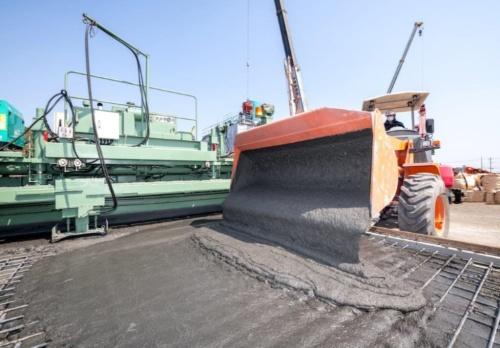実証実験でコンクリート床版にUHPFRCを打設している様子。実現場を想定し、劣化が進んだコンクリート床版の一部をはつった後の鉄筋が露出した状態を再現した(写真:鹿島)
