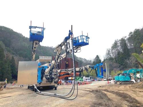 エレクターとコンクリート吹き付け機が一体化した汎用機を改造した。手を加えた箇所を、飛島建設のイメージカラーである青にペイントしている。例えば、型枠内で吹き付けやすいようにノズルが2段階に回転するようにした(写真:飛島建設)