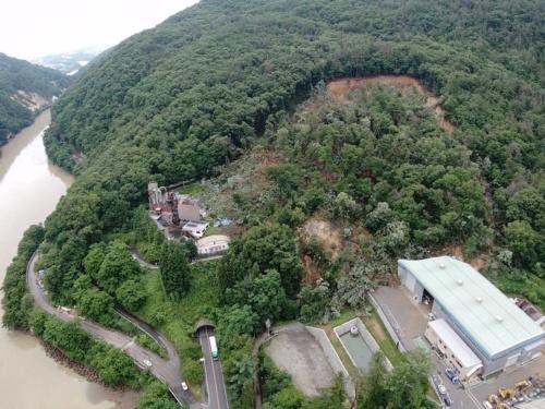 国道19号犬戻トンネルの松本市側坑口付近で発生した地滑り。写真右下の建物が廃棄物処理会社の工場。2021年7月6日午前9時過ぎに撮影(写真:長野県土尻川砂防事務所)