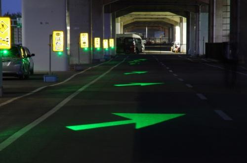 路面に矢印形の光を照射して試験している様子。工事の予告看板1枚につき1個の小型照明装置を取り付ける(写真:阪神高速技術)